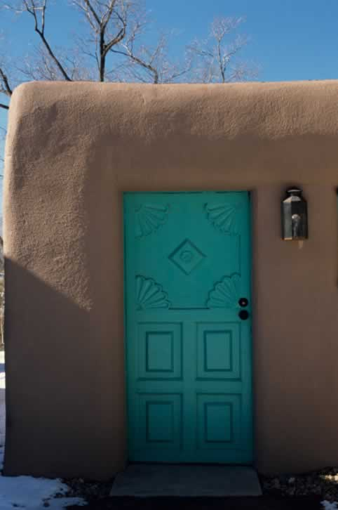Turquoise Exterior Panel Door with Carved Fan Design in Southwest-Style Adobe Home