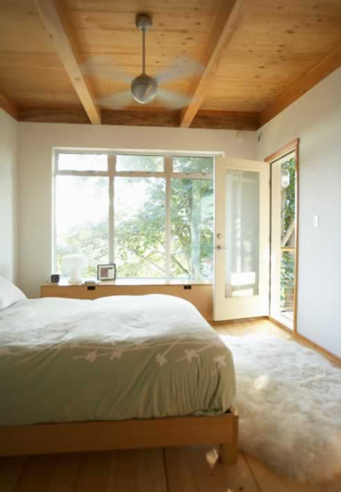 Lofty Windows Make a Bedroom Part of the Forest