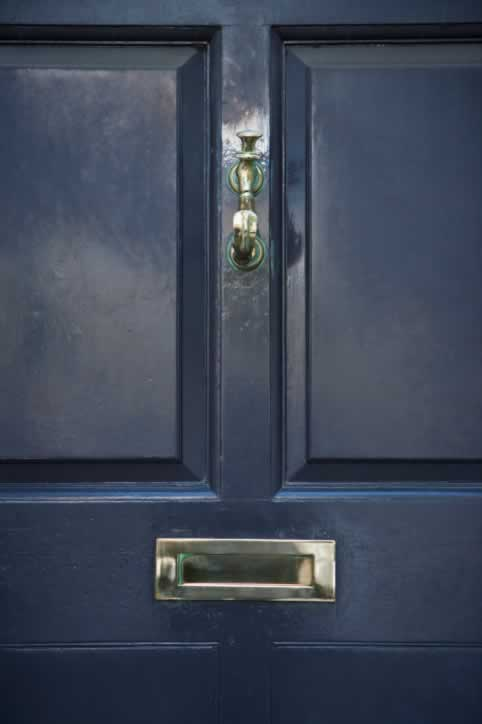 Black Wooden Raised Four Panel Door with Brass Knocker and Mail Slot