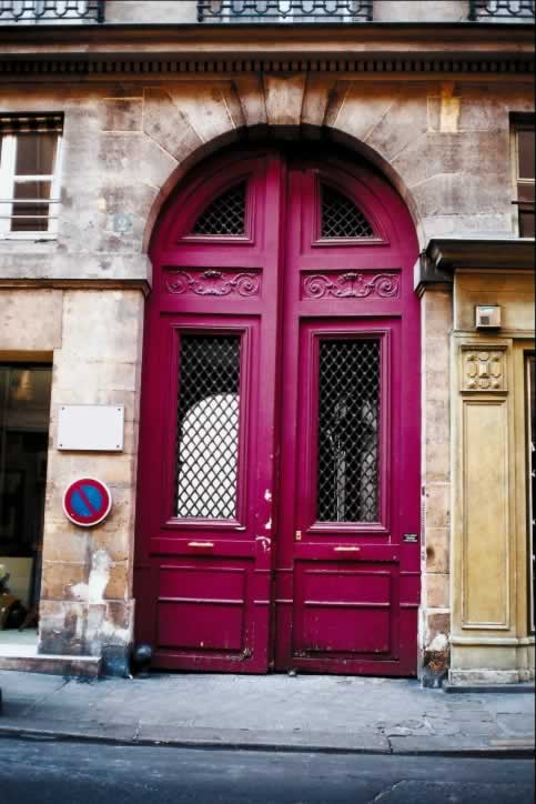 Huge Arched Double Pink Doors Have Windows with Grilles