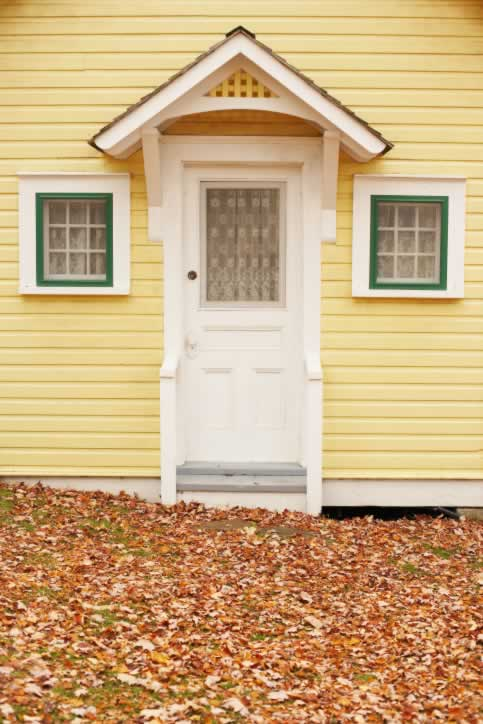 White Three Panel Door to Quaint Home with Yellow Siding