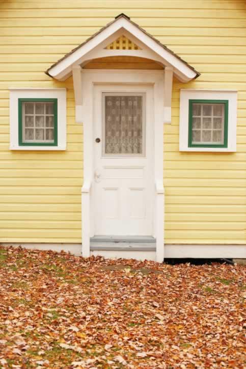 White Three Panel Door to Quaint Home with Yellow Siding