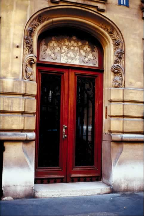 Red french Doors with Brass Handle in Carved Arch Entryway