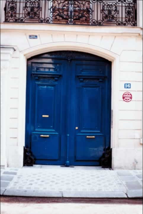 Bold Blue Double Doors Fill White Stone Elliptical Arch